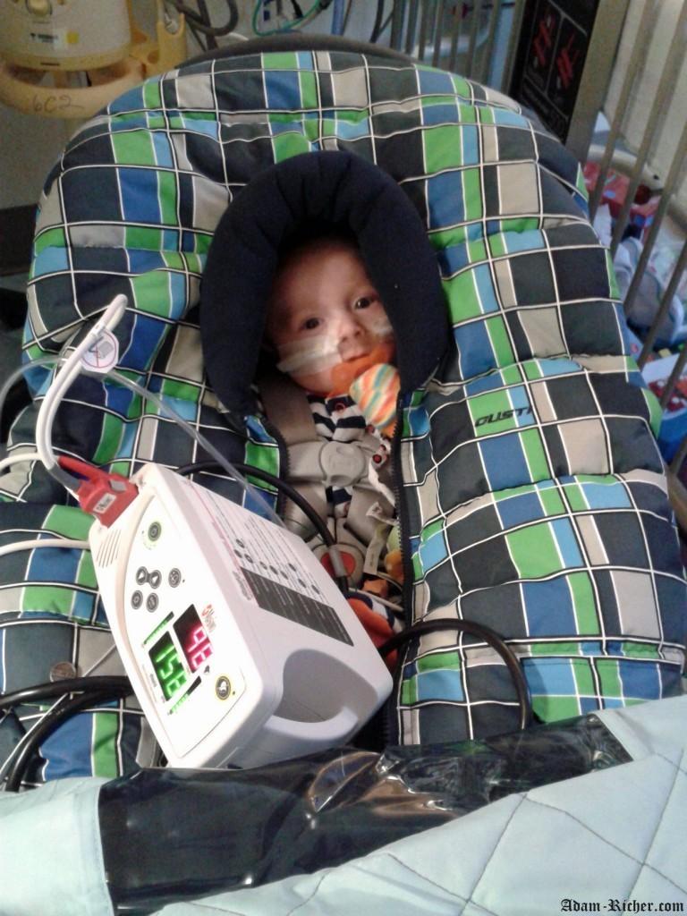Adam dans son banc d'auto avec son saturomètre et son oxygène :  il est prêt pour sa sortie de l'hôpital!